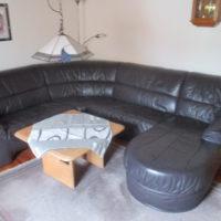 Ledercouch (leicht brombeerfarben / aubergine) mit Tisch und passenden Teppich. Mache ein freiwillig